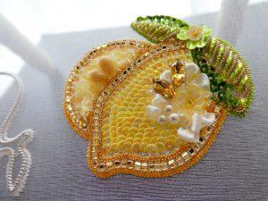 レモンのブローチです。丸ごとレモンの横に半切りレモンがあります。スパンコールで作ったお花の周りにリボンが刺繍してあります。