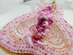 洋梨のブローチです。全体がピンク一色です。洋梨の形にビーズとスパンコールが並んで刺してあります。中央は、リボン刺繍とスパンコールで刺した立体的な小花が縦に並んでいます。