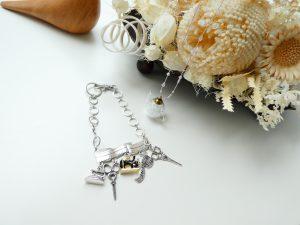 透明なホット型の中にビーズが入っているネックレスと、ハサミやアイロン、ミシンの小さいチャームが付いている、バックチャームです。