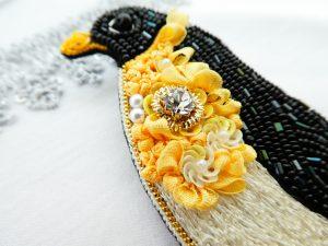 ペンギンのブローチです。胸元に大きなクリスタルとリボン刺繍があり華やかな感じです。