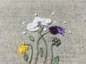 立体的な白いバラと黄色いリボン刺繍の花です。