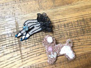 ブローチが2個並んでいます。モコモコの犬と大きなクリスタルリングを付けた右手です。