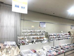 催事でビーズ材料を展示しています。小袋に入ったビーズが平台に並んでいます。