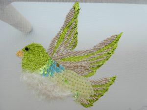 スパンコールとモールと糸刺繍で刺した小鳥です。羽ばたいています。