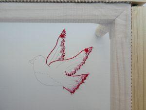 鳥の羽根と尾をビーズで刺しています。