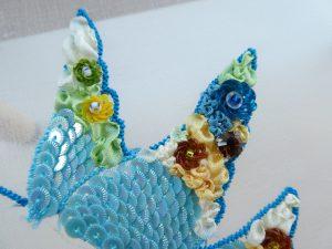 小鳥の羽根先にスパンコールとリボン刺繍があります。