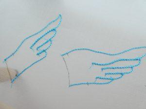 鳥の手羽先の輪郭を糸で刺しています。