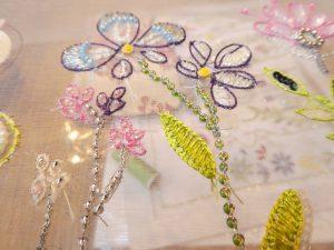 糸刺繍でお花を刺しています。ビーズで茎を刺しています。