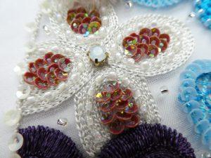 糸刺繍の上にビーズを刺したお花です。
