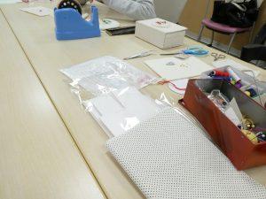 大きなテーブルでビーズ刺繍のレッスンをしています。