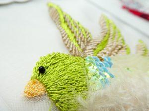 小鳥の顔と羽根をレーヨン糸で刺してます。