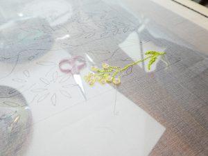 レーヨン糸で刺した茎と葉の上に、スパンコールのお花が咲いてます。