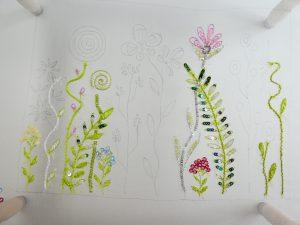 レーヨン糸で繊細な刺繍をしています。数本の茎にサテンステッチで刺した葉があります。