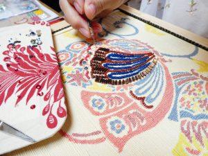 紬の帯にアリワークでビーズ刺繍をしています。蝶の柄です。