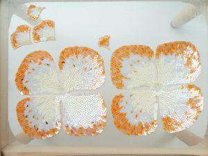 スパンコールでグラデーションをつけながら、4枚の花びらを刺しています。