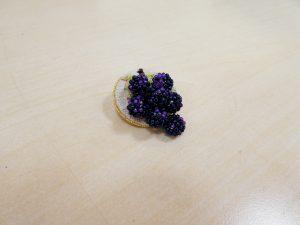 揺れる葡萄の実がついた円形のブローチです。