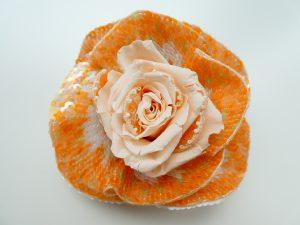 中心にプリザーブドフラワーの薔薇があります。周りとプリザーブドフラワーの中に、ビーズ刺繍した花びらをコラボさせました。