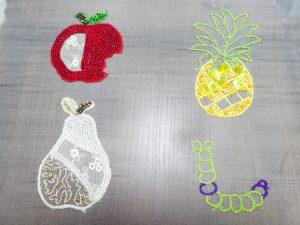 アリワークでリンゴ、パイナップル、洋梨、いも虫のデザインを刺しています。