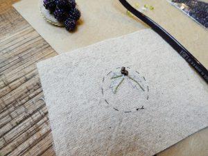 円形のブローチです。糸で葡萄の葉脈を刺しています。