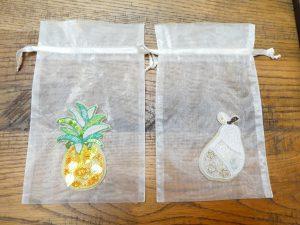 アリワークで刺したパイナップルと洋ナシを袋にアップリケしました。