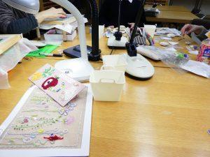 大きなテーブルを囲んでビーズ刺繍のレッスンをしています。