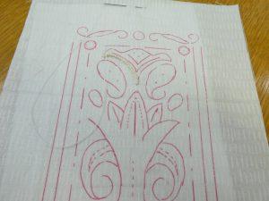 生地に左右対称のデザインが転写されています。上部からビーズを刺しています。