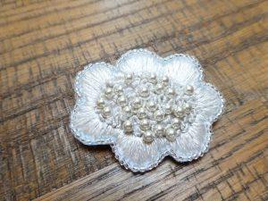 お花のブローチです。艶のある花びらと花芯部分のパールが華やかです。