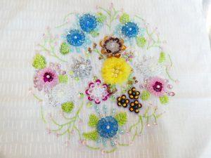 スパンコールやオーガンジーリボンなど様々な材料を使ったお花が刺してあります。パステルカラーなので華やかで春の感じです。