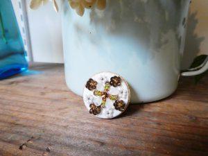 円形の小さなブローチです。スパンコールで立体的なお花を刺繍しています。中心に半透明の可愛いビーズの花びらが4枚あります。