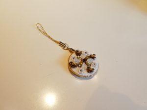円形のストラップです。スイカの種の形のビーズを4枚使って花びらにしました。周りにはスパンコールで刺繍した立体的なお花があります。