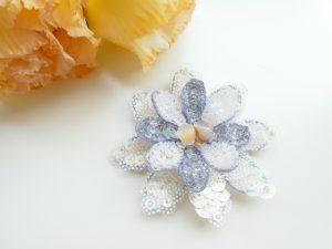 大小の花びらを重ねたブローチです。花芯部分は半透明の勾玉を2個飾っています。