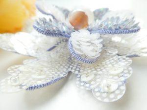 大きな花びらの上に小さい花びらを重ねて、花芯に勾玉を飾りました。