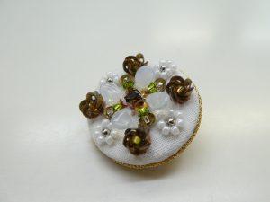 直径3cmのブローチです。中央のビジューの周りにスパンコールで刺繍した立体的なお花と、ビーズの小花があります。