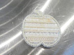 白の単色で作ったリンゴの形のブローチです。ビーズやスパンコールが、横方向に綺麗に並んでいます。