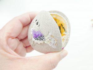 表面にビーズとスパンコールで刺繍した小鳥があります。