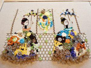 アリワークとリボン刺繍のコラボ作品です。沢山のリボン刺繍をした花のドレスの中に、スパンコールとビジューで刺したお花がキラキラ目立ちます。女性2人がお洒落な傘を刺して並んでいます。