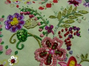 紫の花の横(ピンク小花)と、細長い葉にスパンコールを連続で刺しています。茎の部分はアウトラインステッチや、竹ビーズが刺繍されています。この花模様の刺繍が完成いました。