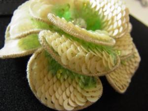 3枚の花びらを重ねたチャームのアップです。4㎜フラット型スパンコールの白とグリーンを使って、重なり合うように刺してあります。