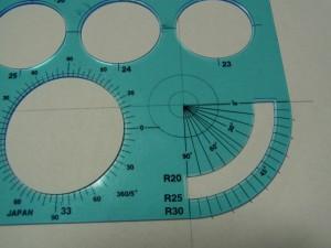 同心円の製図をする為、二重の円を描いています。スケールの角の分度器を使って、角度に印をつけます※何等分に分けるかによって角度が決まります。円の中心と分度器の中心を重ねます。