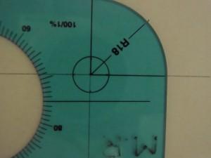 円の中心と分度器の中心を重ねます。スケールの角にある分度器を使い、90度の位置に印をつけます。