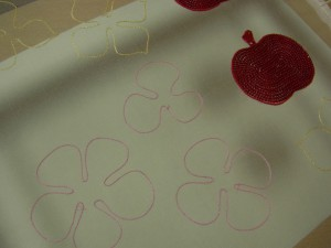 ピンク、黄色の花の輪郭にチェーンステッチを刺しています