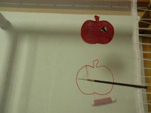 アリワークで、リンゴを赤のビーズで刺し右上に蜂を刺しています。
