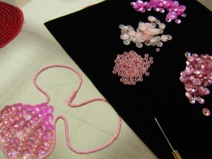 ピンクの花のチャームを、4種類の材料で刺しています