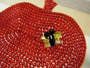 ビーズでリンゴを刺し埋めた中に、蜂を一匹右上に刺しています。