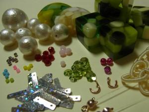 ネックレスを解体した材料がバラバラに置いてあります。ビーズ、スパンコール、コットンパール、アクリルゼリーなどです。