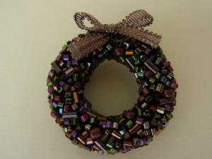 リボンが付いているクリスマスリースのブローチです。紫の竹ビーズが輝いています。