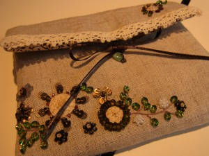 小物入れが完成!刺繍も縫製もきれいです。紐をくるくる巻いた周りに、スパンコールを刺した花があります。