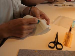 アクリルケースを制作しています。スパンコールを円形に連続刺しをして、可愛い花を2個刺しています。
