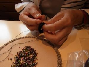 リースのブローチを丸小ビーズ、竹ビーズで刺しています。
