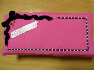 ピンクの生地にリボンと花の刺繍、cocomorのタグが刺してあります。